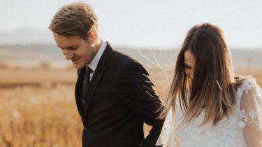 getrouwd koppel loopt hand in hand door een graanveld