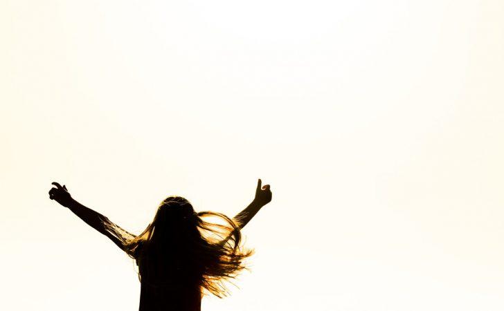 Blij meisje zwaait met handen in de lucht