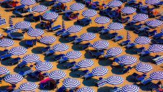 Strand bezaaid met bedjes en parasollen
