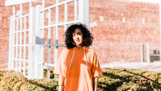 meisje met oranje trui kijkt serieus
