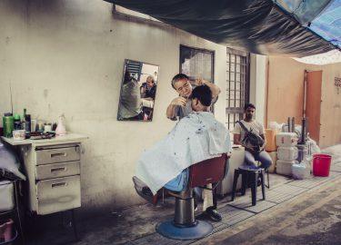 barber bezig met een klant, hairdresser, gevluchte kappers