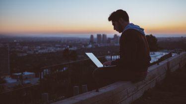 jongen zit op muurtje met laptop