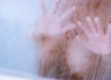 vochtige douchedeur met vrouwenhanden erop