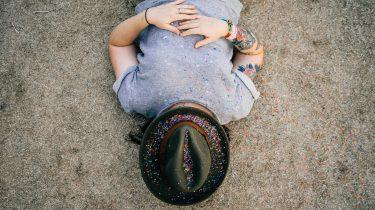 meisje met hoed ligt op strand