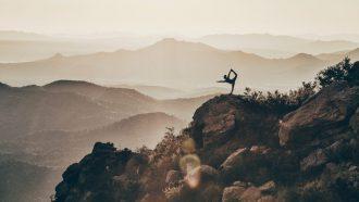 iemand doet yoga pose op berg