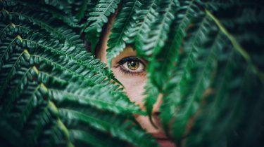 meisje achter bosje