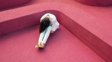meisje zit in roze hoek