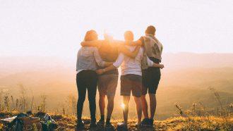 groep vrienden omhelzen elkaar bij zonsondergang