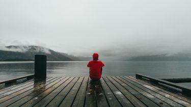 persoon zit alleen op steiger en is eenzaam