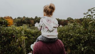 meisje op schouders vader