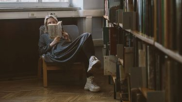 meisje zit in een stoel en leest een boek